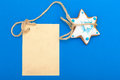 Christmas gingerbread cake star with icing and decoration and blank card homemade blue paper copy space on blue as background Royalty Free Stock Photography