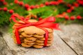 Christmas gingerbread cookies on a rustic wooden background with red ribbon