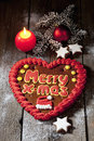 Christmas gingerbread heart with candle cinnamon stars pine twig christmas bulb on wooden floor Royalty Free Stock Photo