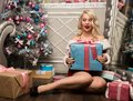 Christmas girl with gifts near the Christmas tree. woman dressed as Santa Royalty Free Stock Photo