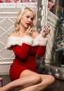 Christmas girl with gifts sitting near mirror and paints lips with lipstick. woman dressed as Santa Royalty Free Stock Photo