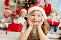 Christmas girl image of adorable in santa cap looking at camera with company of friends behind Royalty Free Stock Image