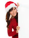 Christmas girl peeking from behind blank sign billboard advertising photo of young smiling santa woman in santa hat showing paper Stock Photos