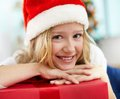 Christmas girl portrait of cheerful with red giftbox looking at camera on evening Stock Image