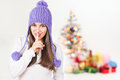 Christmas girl with purple beanie gesturing hush cute young caucasian woman hat smiling looking at camera colorful decorated tree Royalty Free Stock Images