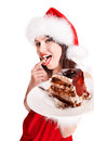 Christmas girl in santa hat eat cake red eating on plate isolated Royalty Free Stock Photography