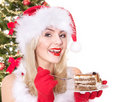 Christmas girl in santa hat eating cake. Stock Photo