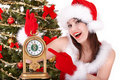 Christmas girl in santa hat holding alarm clock. Royalty Free Stock Image