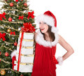 Christmas girl in santa holding stack gift box hat near tree isolated Royalty Free Stock Photos