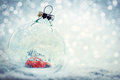 Christmas glass ball in snow with miniature winter world inside Royalty Free Stock Photo