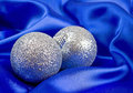 Christmas glitter balls on blue satin Royalty Free Stock Image