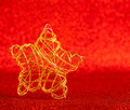 Christmas gold wire star on red glitter Stock Images