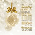 Christmas greeting card - patterned bauble with glitter gold bow hanging on a christmas tree and type design greeting. Royalty Free Stock Photo