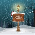 Christmas greeting card - snowy winter landscape background. Street lamp and wood board with merry christmas calligraphy Royalty Free Stock Photo