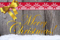 Christmas greetings on wooden board with golden bow and red white fabric ribbon Royalty Free Stock Photo