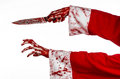 Christmas and halloween theme santa s bloody hands of a madman holding a bloody knife on an isolated white background studio Stock Image
