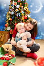 Christmas happy young woman with a child beautiful women on the background of the tree Stock Image