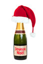 Christmas hat on a Champagne bottle Joyeux Noel (merry christmas), isolated on white Royalty Free Stock Photo
