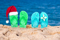 Christmas hat on flip flops in the sand Royalty Free Stock Photo