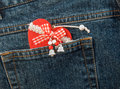 Christmas heart tucked into denim trouser pocket red wooden with ribbons and bells Royalty Free Stock Photography