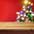 Christmas holiday background with empty wooden deck table over Christmas tree bokeh. Ready for product montage Royalty Free Stock Photo