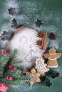Christmas and holiday baking background. Fir trees with decoration,  flour, spices and cookies molds on a cutting board. Royalty Free Stock Photo