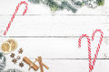Christmas holiday frame with candy canes and fir branches on woo Royalty Free Stock Photo