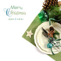 Christmas holiday green theme table place setting traditional with fine china on white background with merry sample text Stock Image
