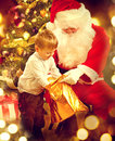 Christmas holiday scene. Cute little boy and Santa Claus Royalty Free Stock Photo