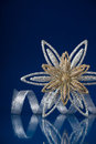 Christmas holiday snowflake and silver ribbon on dark blue background Royalty Free Stock Photo