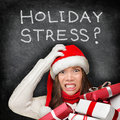 Christmas holiday stress stressed shopping gifts woman for holding presents wearing red santa hat looking angry and Royalty Free Stock Photo