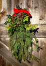 Christmas holiday wreath decoration old barn door fashioned country pendant arrangement with evergreen branches and holly Royalty Free Stock Photo