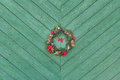 Christmas Holyday Advent wreath hanging outside at green wooden door background
