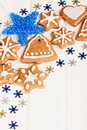 Christmas homemade gingerbread cookies and blue decoration over white wooden board Stock Image