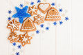 Christmas homemade gingerbread cookies and blue decoration over white wooden board Royalty Free Stock Images