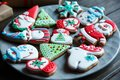Christmas homemade gingerbread cookies, spices on the plate on dark wooden background among Christmas presents