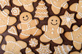 Christmas homemade gingerbread couple, firs, stars cookies over wooden background