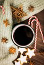 Christmas hot steaming cup of glint wine with spices, anise, cookies in a shape of star, red candies, pepper and gray scarf on