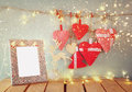Christmas image of fabric red hearts and blank frame, garland lights, hanging on rope in front of blue wooden background Royalty Free Stock Photo
