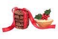 Christmas indulgence mince pie and chocolate chip cookie biscuit stack with merry red ribbon and holly over white background Royalty Free Stock Photos