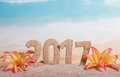 Christmas inscription 2017 in sand decorated with tropical flowers on a background of the sea