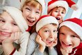 Christmas joy group of excited kids in santa caps looking at camera Royalty Free Stock Images