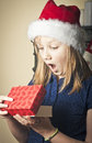 Christmas joy portrait of a young girl at opening her present Royalty Free Stock Image