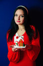 Christmas joy studio portrait of a young woman holding miniature decorated house in her hands Royalty Free Stock Photo