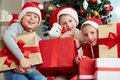 Christmas kids group of three little boys in santa caps looking at camera while sitting by xmas tree Royalty Free Stock Photography