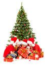 Christmas kids opening presents gift box sitting under fir tree in santa hat red over white background new year Stock Photography