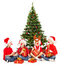 Christmas kids playing under fir tree new year presents over white background in red santa hat and accessories Royalty Free Stock Image