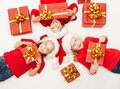 Christmas kids with red presents gift box in santa hat lying down on white floor top view Royalty Free Stock Images