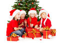 Christmas kids in santa hat with presents figts sitting under fir tre red gifts boxes tree over white background Stock Image