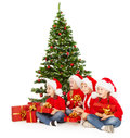 Christmas kids in santa hat with presents sitting under fir tre red gift boxes tree white background Stock Photo